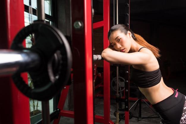 Mujer asiática que descansa después de ejercicios agazapados en gimnasio, mujeres de la aptitud en el centro de aptitud.