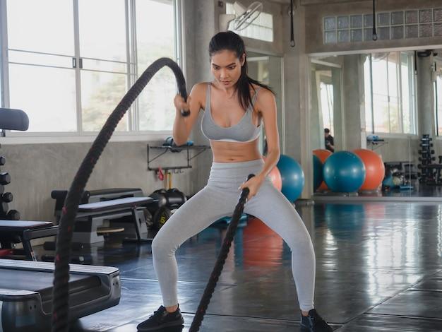 Mujer asiática que ejercita con las cuerdas de la batalla en el gimnasio