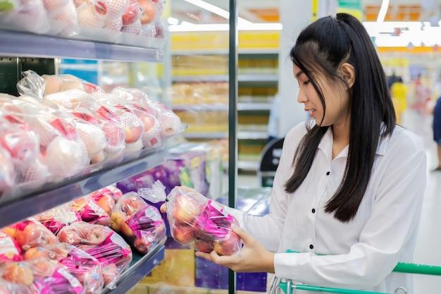 Mujer asiática que elige la manzana de la fruta de la tienda con el carro de la compra en supermercado. compras en concepto de supermercado.