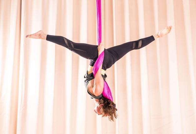 Mujer asiática que entrena en sala de fitness con elementos de yoga mosca