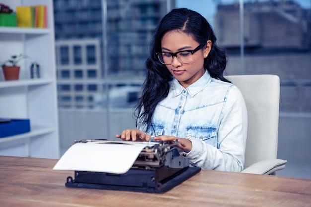 Mujer asiática que escribe a máquina en oficina