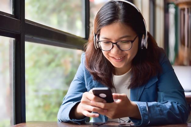 Mujer asiática que escucha la música con el auricular.