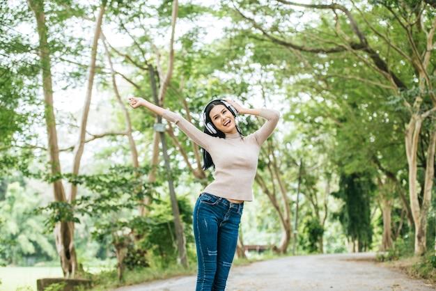 Mujer asiática que escucha la música preferida en los auriculares. tiempo feliz y relajarse