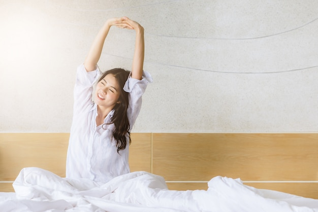 Mujer asiática que se extiende en la cama después de despertarse en la mañana con la luz del sol
