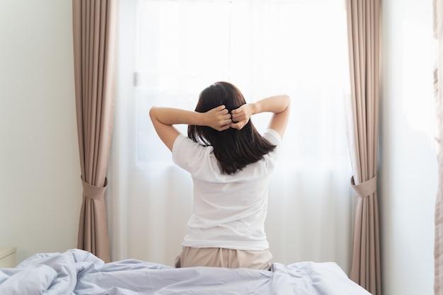 Mujer asiática que se extiende en el dormitorio después de despertarse, vista posterior