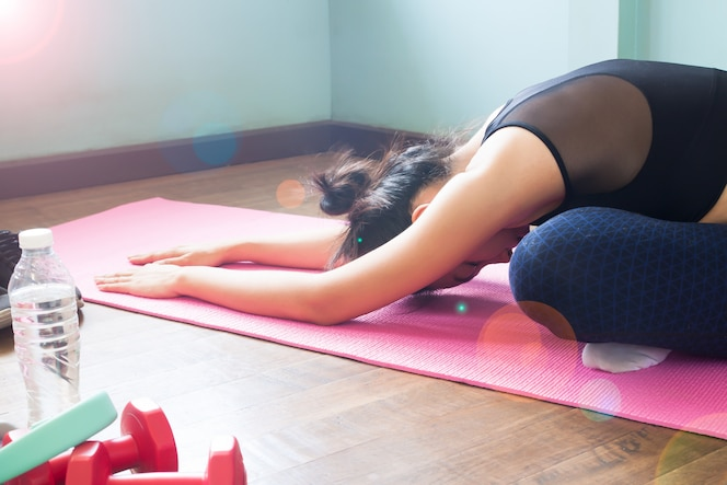 Mujer asiática que hace yoga en ejercitar la estera