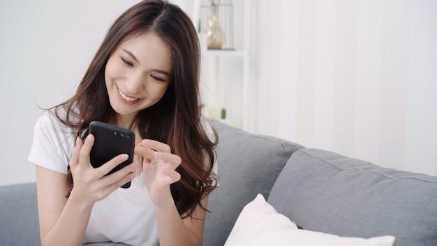 Mujer asiática que juega smartphone mientras que miente en el sofá casero en su sala de estar.
