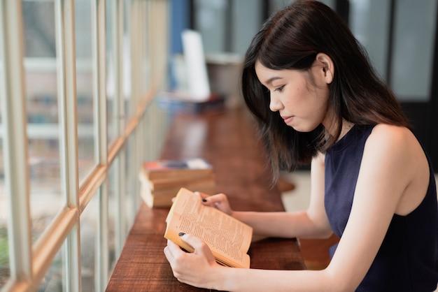 Mujer asiática que lee un libro en el coffeeshop.