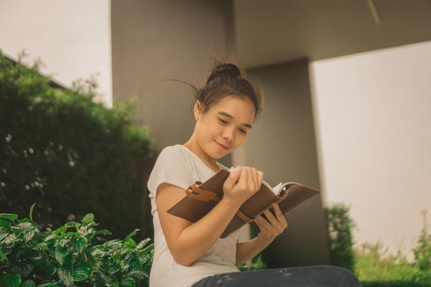 Mujer asiática que lee un libro en parque con los rascacielos en el fondo
