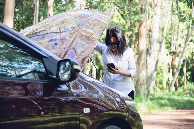 Mujer asiática que llama al reparador o al personal de seguros para arreglar un problema del motor del automóvil en una carretera local