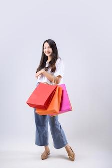 Mujer asiática que lleva una bolsa de compras multicolor sobre fondo blanco.