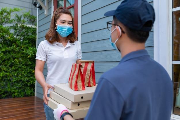 Mujer asiática que llevaba una máscara que recibía un paquete de alimentos del repartidor en el servicio de concepto en casa del virus de coronavirus pandémico en cuarentena [covid-19]