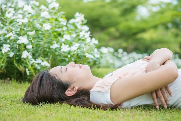 Mujer asiática que miente y que duerme en campo de hierba después de que ella cansara por la tarde