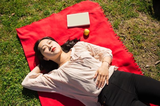 Mujer asiática que miente y que duerme en césped
