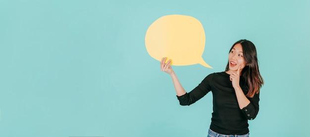 Mujer asiática que mira el bocadillo de diálogo