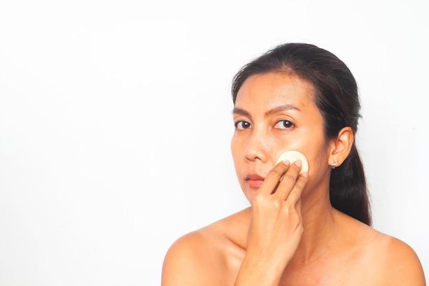 Mujer asiática que mira la cámara y que aplica el polvo de la fundación en su cara. concepto de belleza