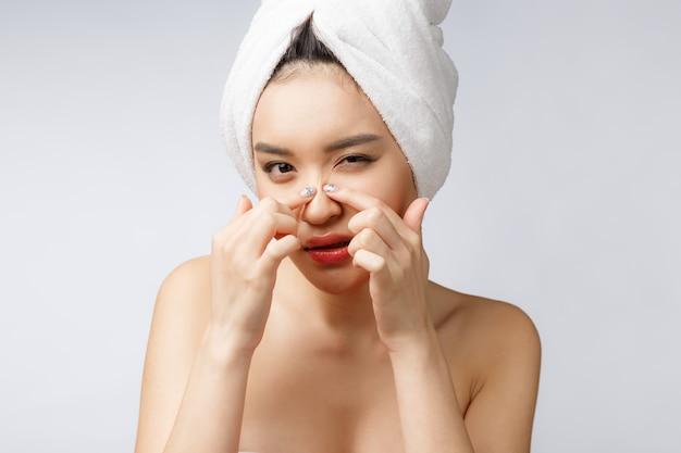 Mujer asiática que mira la espinilla en cara. mujer joven intenta quitarle la espinilla
