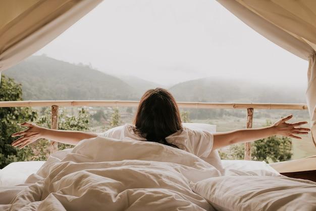 Mujer asiática que mira mountain view de la tienda en tiempo de la puesta del sol
