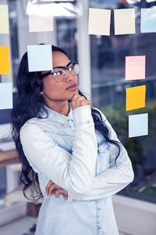 Mujer asiática que mira notas pegajosas en la pared de cristal