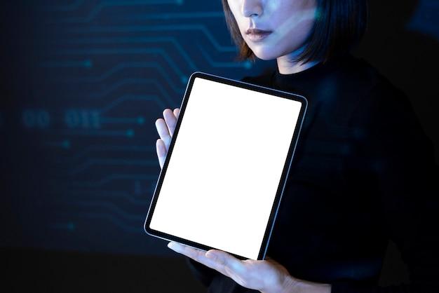 Mujer asiática que muestra la tecnología futura innovadora de la tableta de la pantalla en blanco
