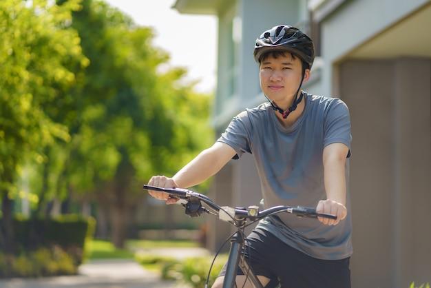 Mujer asiática que parece feliz mientras anda en bicicleta por su vecindario para la salud y el bienestar diario, tanto físico como mental.