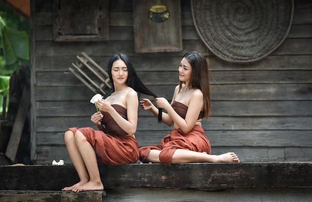 Mujer asiática que peina el balneario del pelo en el vestido del estilo del drama que se sienta en casa tailandesa vieja