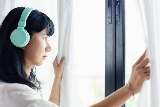 Mujer asiática que se queda en casa, usando audífonos y parada distraída en la puerta para el auto-cuarentena y el distanciamiento social en coronavirus o el concepto de situación de brote covid-2019