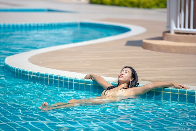 Mujer asiática que se relaja en la piscina.