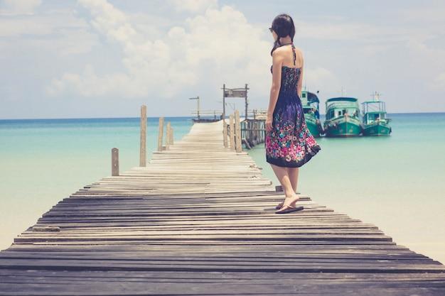 Mujer asiática que se relaja en el puente en la playa tropical.