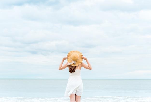 La mujer asiática que respira para el aire fresco se siente relajante y feliz sobre el verano del mar / de la playa