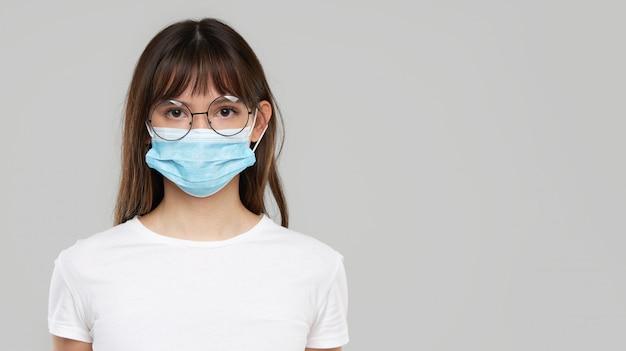 Mujer asiática que se siente mal y que lleva la máscara protectora de la cara en fondo gris del estudio. copiar espacio para texto. la primera defensa contra la epidemia de gripe y coronavirus.
