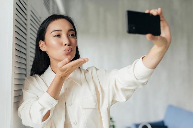 Mujer asiática que sopla un beso a sus seguidores