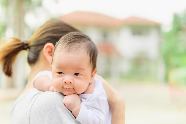 Mujer asiática que sostiene a un bebé recién nacido en sus brazos en casa. día de la madre y concepto recién nacido del cuidado de la salud del bebé recién nacido.