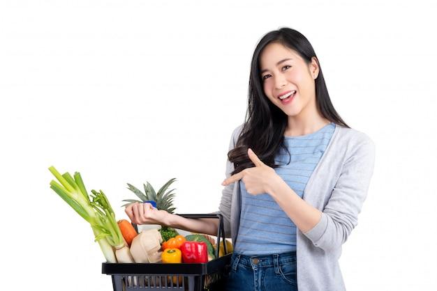 Mujer asiática que sostiene la cesta de compras llena de verduras y comestibles