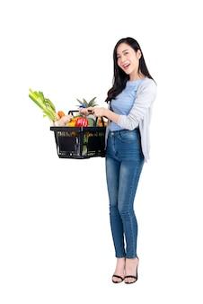 Mujer asiática que sostiene la cesta de compras del supermercado llena de ultramarinos