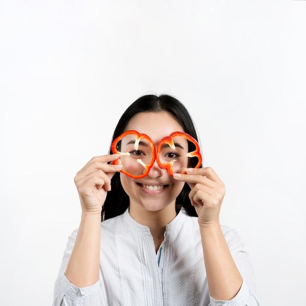 Mujer asiática que sostiene dos rebanadas de pimientos rojos delante de sus ojos sobre la superficie blanca
