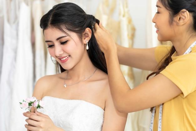 Mujer asiática que sostiene la flor que mide en el vestido de boda en una tienda del sastre.