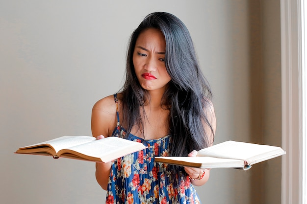 Mujer asiática que sostiene los libros