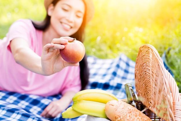 Mujer asiática que sostiene la manzana en la mano