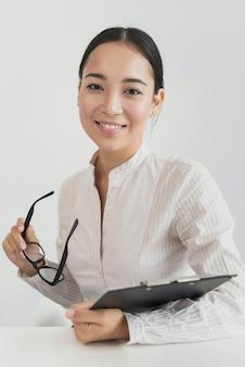 Mujer asiática que sostiene un portapapeles