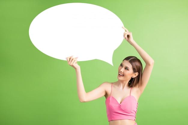 Mujer asiática que sostiene y que mira para arriba a la burbuja del discurso con el espacio vacío para el texto en verde
