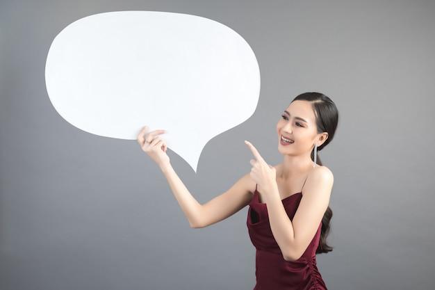 Mujer asiática que sostiene y que mira para arriba a la burbuja del discurso con el espacio vacío para el texto
