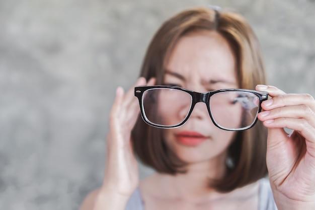 Mujer asiática que tiene dolor de cabeza de anteojos