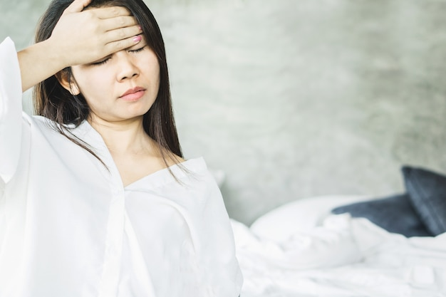 Mujer asiática que tiene dolor de cabeza por la mañana