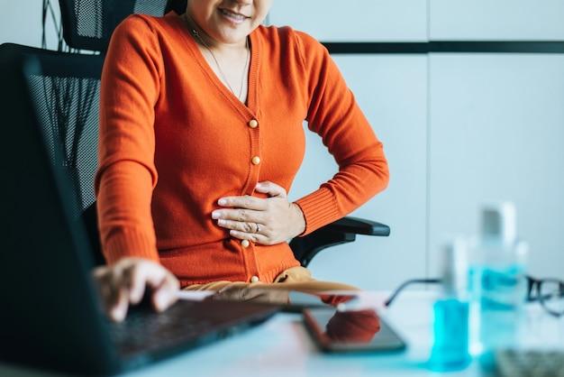 Mujer asiática que tiene dolor de estómago doloroso durante el trabajo desde casa
