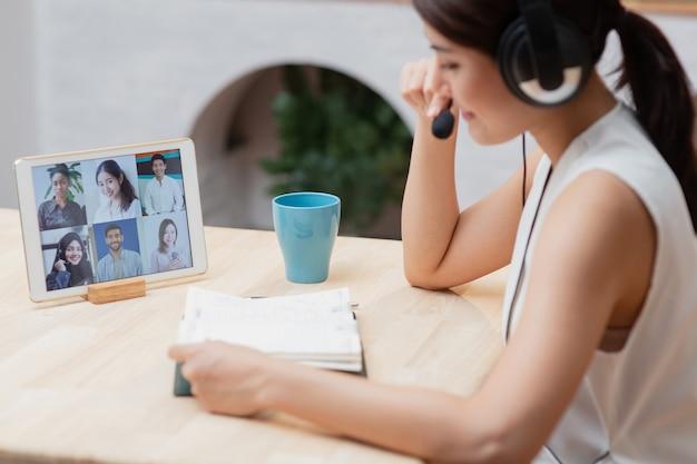 Mujer asiática que trabaja desde casa con reunión en línea de conferencia de videoconferencia con el equipo de colega de diversidad usando laptop