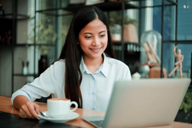 Mujer asiática que trabaja con la computadora portátil en la cafetería cafe
