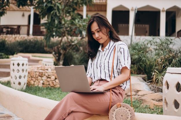 Mujer asiática que trabaja en la computadora portátil en vacaciones