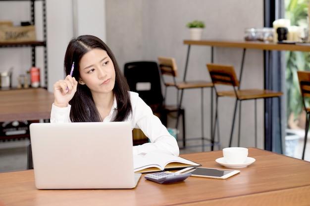 La mujer asiática que trabaja en línea con la computadora portátil y piensa el proyecto para la idea en la tienda moderna del café.