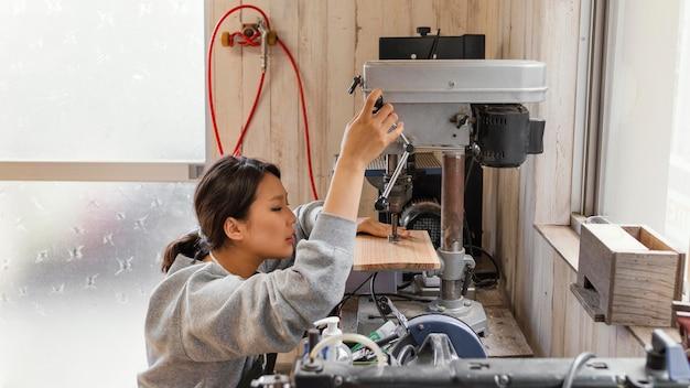Mujer asiática que trabaja con madera tiro medio